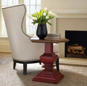 beige chair and end table with flowers in vase in living room