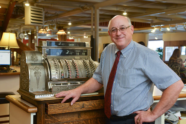 Fourth generation owner Brad Fitterer at the store's original brass cash register.